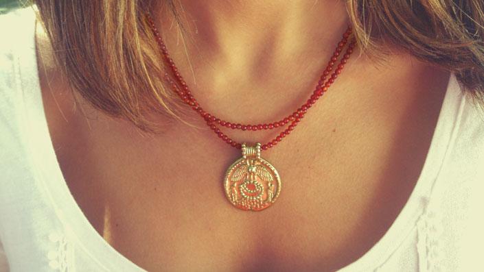 Colgante Disco alado símbolo del sol que significa potencia divina y humana.
